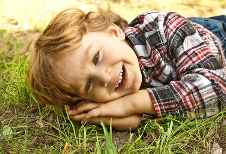 Portrait of a little smiling blond boy lying in the grass photo