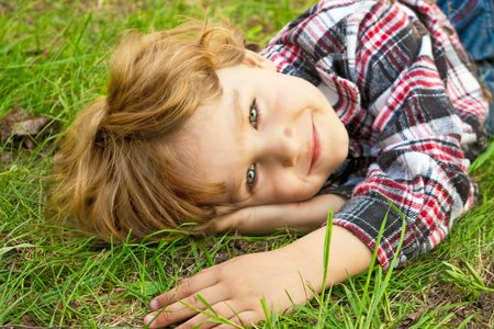 Portrait of a little smiling blond boy in the garden photo