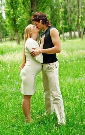Beautiful pregnant woman with her husband kissing in the park photo