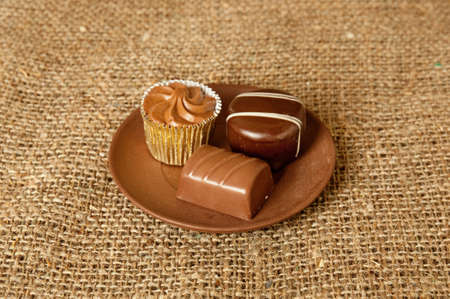 Chocolate sweets on the dish and sack background photo