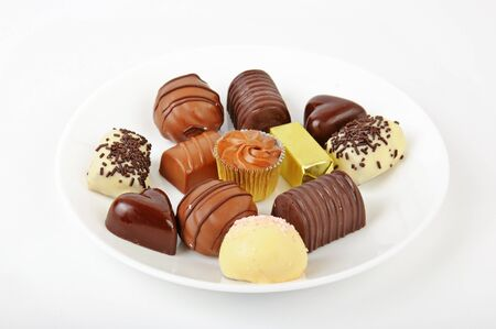 Various kinds of chocolate sweets on the clay dish photo