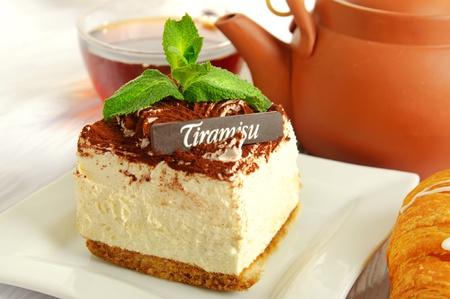 Chocolate tiramisu cake with cup of tea on white photo