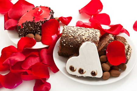 Heart shaped brownie with cake on the dish with rose petals photo