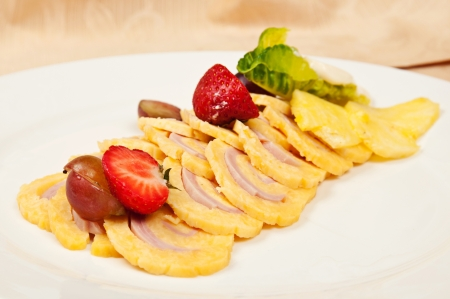 Roll with chiken and cheese decorated with strawberry, lettuce, grape on dish in restaurant