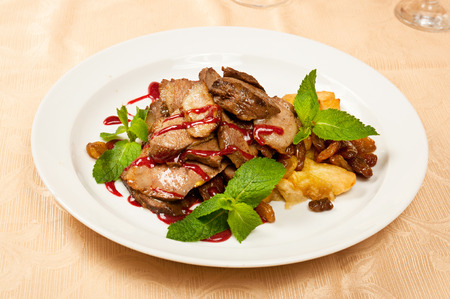 Roasted sliced goose with mint on dish in restaurant photo