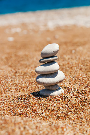 Cairn (pile from stones) on the beach sand near sea, harmony and stability concept photo