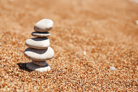 Cairn (pile from stones) on the beach sand near sea, harmony and stability concept