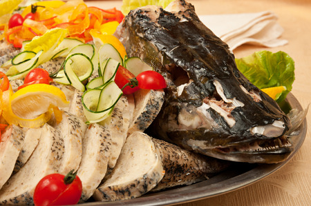 Stuffed sliced pike with head, decorated with tomato, lemon and cucumber close up in restaurant photo