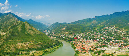 Old georgian town  Mtskheta in the mountains with blue sky and green hills photo