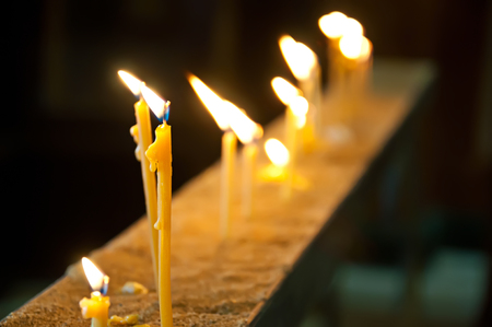 Burning candles in the church, religion dark background photo