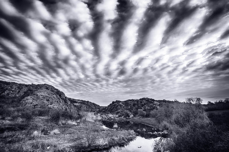 Sunrise at canyon with river, hills and dramatic sky with reflection (black  white version) photo