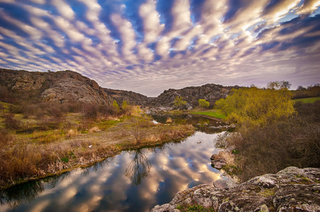 Sunrise at canyon with river, hills and dramatic sky with reflection photo