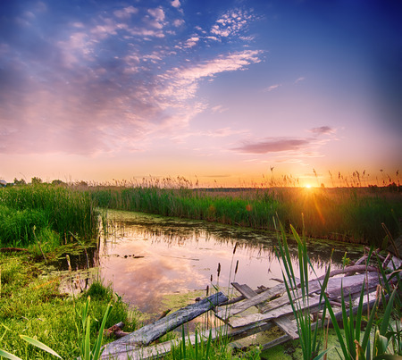 Rural summer sunrise landscape with river, wooden bridge  and dramatic colorful sky photo