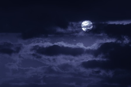 heaven on earth: The moon on the dark sky among the clouds, natural abstract blue background