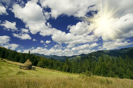 haymow: Carpathian mountains summer  landscape with blue sky, clouds, sun and haystack, natural summer background