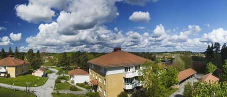 urban idyll: Panoramic view of typical small swedish town at summer time with blue sky and clouds