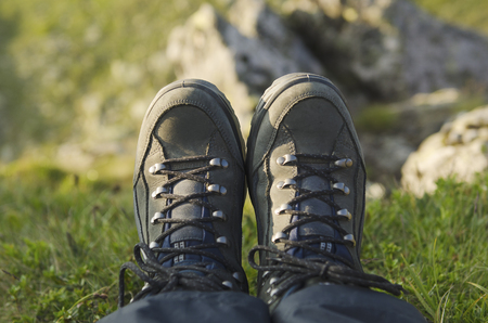 summer shoes: Trekking boots  in the mountains against precipice, travel healthy active lifestyle background