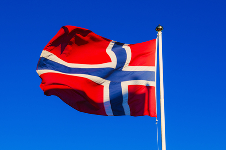 flagpoles: Flag of Norway against the blue sky, national patriotic background