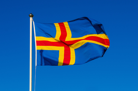 flagpoles: Flag of Aland Islands against the blue sky, national patriotic background Stock Photo