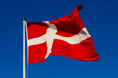 flagpoles: Flag of Denmark against the blue sky, national patriotic background Stock Photo