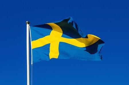 flagpoles: Flag of Sweden against the blue sky, national patriotic background