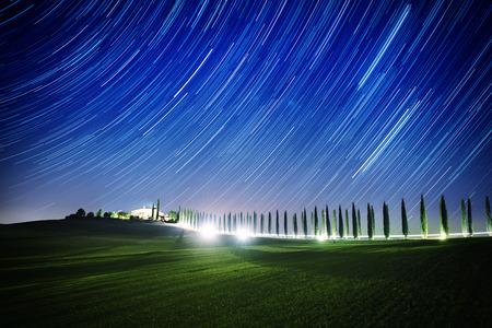 Bellissimo paesaggio notturno in Toscana con tracce di stelle sul cielo, cipressi e splendente strada nel prato verde. Fantastico sfondo naturale all'aperto.
