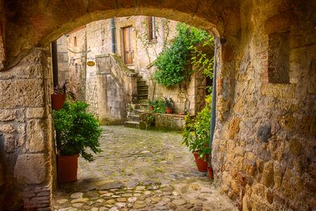 Smalle straat van de middeleeuwse stad Sorano tufsteen met boog, groene planten en geplaveide, reizen Italië achtergrond Stockfoto