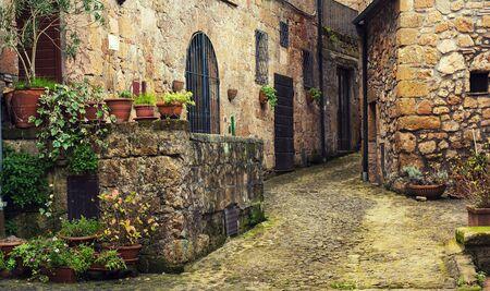 italy street: Narrow street of medieval ancient tuff city Sorano with green plants and cobblestone, travel Italy background