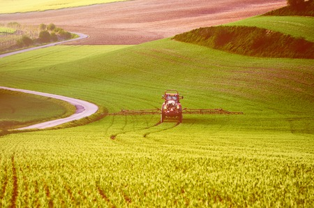 farm machinery: Farm machinery spraying insecticide to the green field, agricultural natural seasonal spring background, vintag retro hipster style