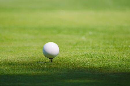 achivement: Golf ball on the green lawn background, sunny natural sport image. Competition, achivement and target concept.