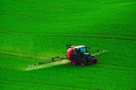 agricultural farm land: Farm machinery spraying insecticide to the green field, agricultural natural seasonal spring background