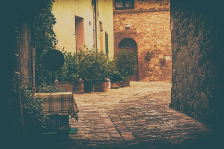 italy background: Empty street of small Tuscany town San Quirico dOrcia in the morning fog, romantic travel vintage hipster european italy background Stock Photo