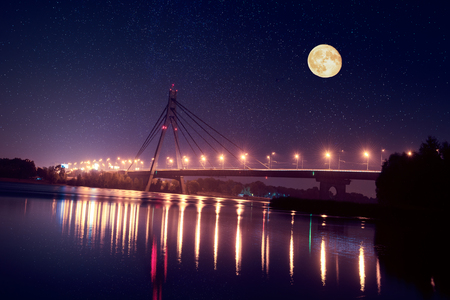 Moscow bridge in Kiev at night with colorful illumination and reflection in Dnieper river and big moon Stock Photo