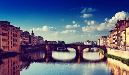 ponte vechio: View from the river to the famous italian medieval bridge - Ponte Vecchio in Florence with blue sky and clouds, travel outdoor Italy sightseeing background Stock Photo