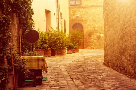 italy background: Empty street of small Tuscany town San Quirico dOrcia with sun shine, romantic travel vintage hipster european italy background