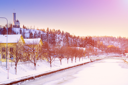 urban idyll: View of small swedish european town Soderhamn with frozen river at sunrise, winter seasonal background