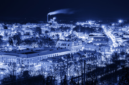 urban idyll: View of small swedish european town Soderhamn at night, industrial background with evening illumination in blue colors