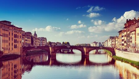 View from the river to the famous italian medieval bridge - Ponte Vecchio in Florence with blue sky and clouds, travel outdoor Italy sightseeing background Stock Photo
