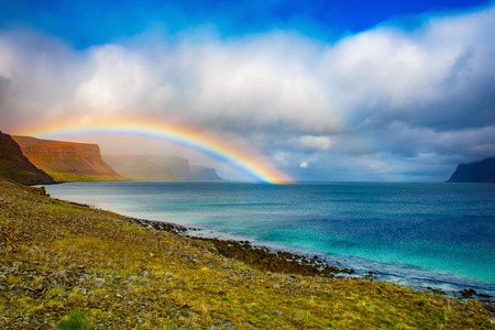 Amazing summer landscape with blue sea, white clouds and rainbow. Iceland, Europe