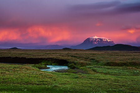 Beautiful volcanic mountain in Iceland covered with snow in pink sunset light