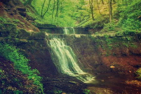 Beautiful mountain rainforest waterfall with fast flowing water and rocks, long exposure. Natural seasonal travel outdoor background in hipster vintage style Stockfoto