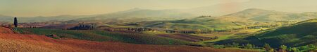 Wavy fields in Tuscany at sunset, Italy. Panoramic view. Natural outdoor seasonal autumn background. Imagens