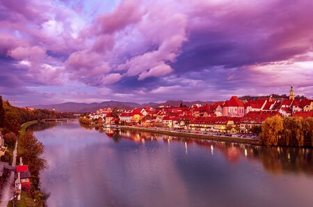 Beautiful view of Maribor city, Slovenia, at sunrise, with river and dramatic sky. Travel outdoor landscape. Stock fotó