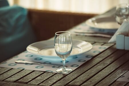 Empty dishware table set in restaurant with glass and plate, summer romantic style in blue and brown colors Reklamní fotografie