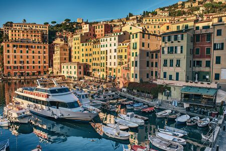 Scenic Mediterranean riviera coast. Sunset view of Camogli town in Liguria, Italy. Travel background with colorful houses and boats.