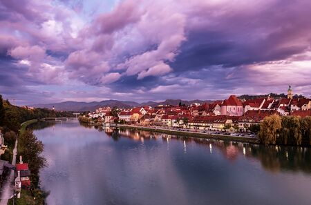 Beautiful view of Maribor city, Slovenia, at sunrise, with river and dramatic sky. Travel outdoor landscape.