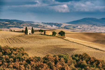 Wavy fields in Tuscany at sunset, Italy. Natural outdoor seasonal autumn background.