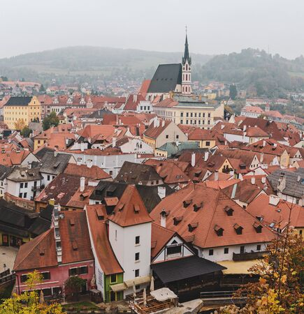 Cesky Krumlov - a famous czech historical beautiful town from above, travel background with red roofs and chapel