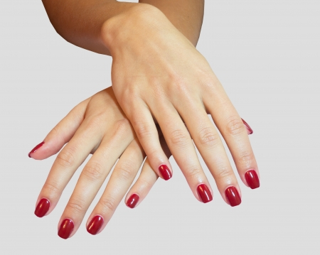 laque: Young woman hands with red manicure over isolated grey background