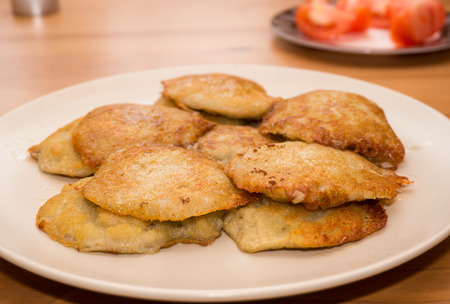 fried potato pancakes on a white plate, woden table photo